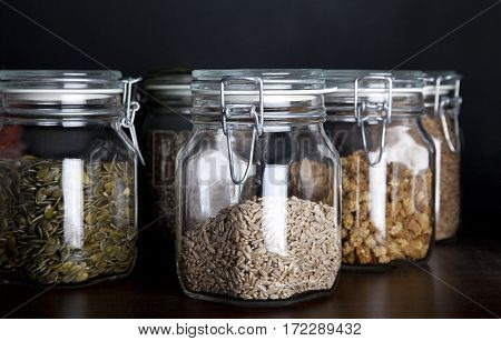 Pumpkin seed sunflower seed and mulberries in glass jars with black background