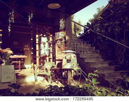 Old wooden house with light shining from the sun. The motorcycle parking.