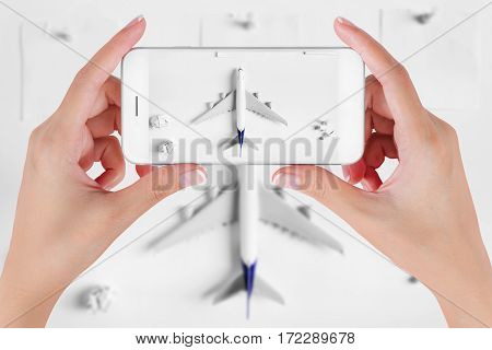 Woman hand using smart phone taking photo for preparation and to do list traveling with blank paper noted paper ball airplane push pin. Travel concepts Ambient blurry background.