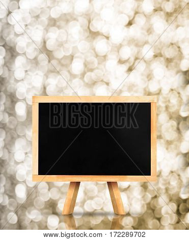 Blackboard With Easel At Gold Sparkling Bokeh Light Background,mock Up For Adding Your Content