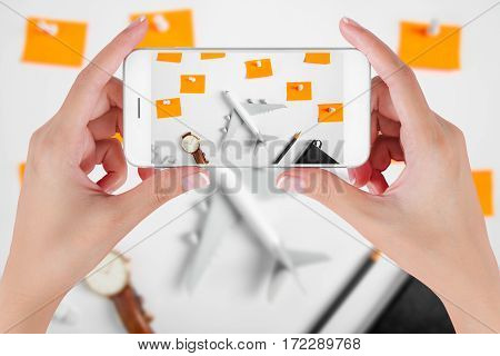 Woman hand using smart phone taking photo for preparation traveling and to do list the paper noted airplane pencil book earphone and push pin. Travel concepts Ambient blurry background.