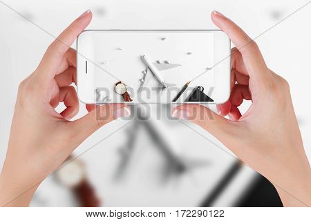 Woman hand using smart phone taking photo for preparation traveling with watch airplane pencils book earphone and push pin Travel concepts Ambient blurry background.