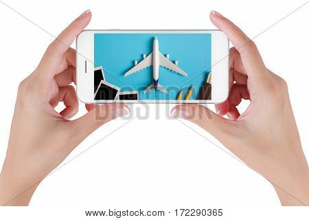 Woman hand using smart phone searching Preparation for Traveling with Blank photograph airplane money passport pencils and book. Travel concepts Isolated on white background.