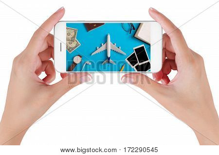 Woman hand using smart phone searching Preparation for Traveling with watch airplane money passport pencils book earphone Blank photograph and eyeglass Isolated on white background.