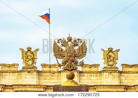 Coat of arms Russian Federation. Coat of arms on background of parapet administrative building government with USSR symbols Russian flag. Selective focus.