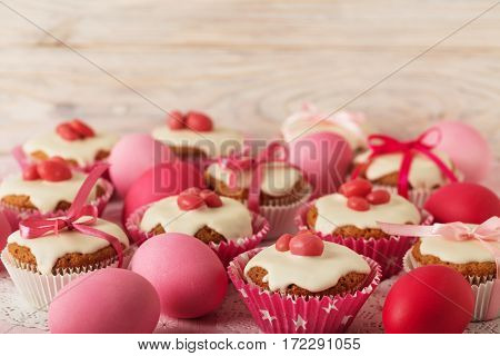 Easter cupcakes with white icing decorated with pink candy and ribbons. Selective focus.