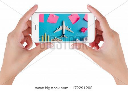 Woman hand using smart phone searching Preparation for Traveling with Blank paper noted airplane money pencils paper ball and push pin. Travel concepts Isolated on white background.