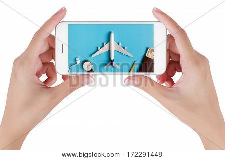 Woman hand using smart phone searching Preparation for Traveling with watch airplane money passport pencils and book. Travel concepts Isolated on white background.