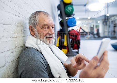Fit senior man in sports clothing in gym resting after working out, towel around his neck, holding smart phone, texting
