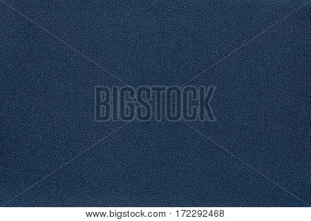abstract speckled texture and background of textile material or fabric of dark blue color