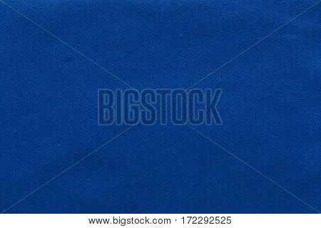 abstract background and texture of denim fabric or textile material of dark blue color