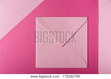 Pink square envelope on pink paper background