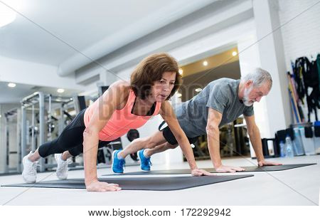 Beautiful fit senior couple in gym working out, doing push ups.