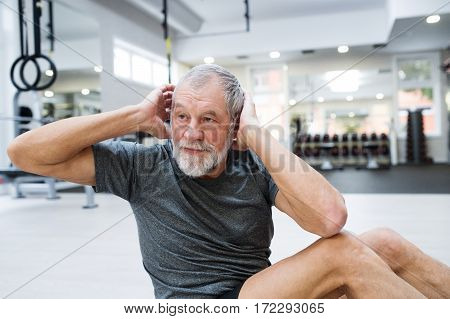 Fit senior man in gym in sports clothing working his abs, doing abdominal crunches.