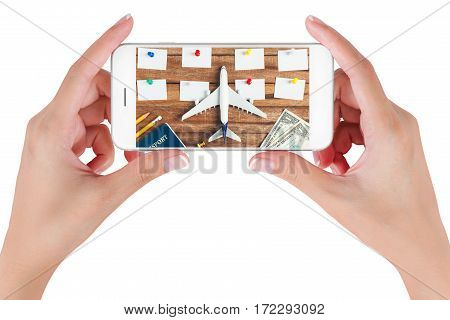 Woman hand using smart phone searching Preparation traveling and to do list with paper noted pencil money passport airplane colorful push pin on vintage wooden background. Travel concepts.