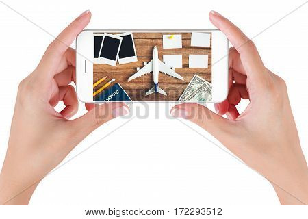 Woman hand using smart phone searching Preparation traveling and to do list with paper noted pencil money passport airplane push pin and blank photographs on vintage wooden background.