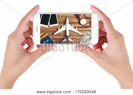 Woman hand using smart phone searching Preparation traveling with pencil money passport airplane watch eyeglasses and photo frame on vintage wooden background. Travel concepts.
