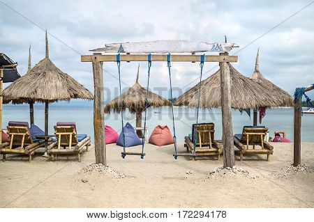 Wooden swing on the beach on the background of the sea and cloudy sky. Behind it there are wooden sunbeds with pillows, straw umbrellas and poufs. Horizontal.