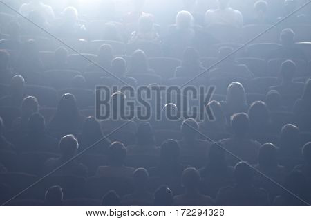 Cinema or theater audience in the screen light. Cinema hall with audience. Cinema auditorium with people in chairs watching movie. The audience watching a motion picture or movie. For use as a background