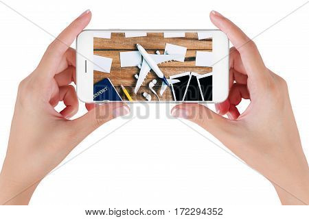 Woman hand using smart phone searching Preparation traveling and to do list with paper noted airplane photo frame earphone pencil and passport on vintage wooden background. Travel concepts.