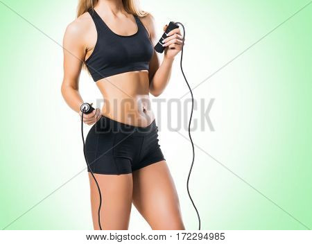 Fit, healthy and sporty woman in sportswear over green background.