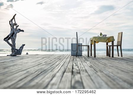 Decorated table with two chairs on the wooden platform on the beautiful background of the ocean and the cloudy sky. There is a tree on the left side and a wicker basket next to the table. Horizontal.