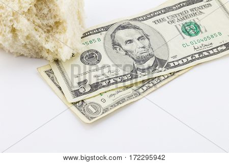 Piece of bread and dollar bills on white background - Conceptual image depicting povery in America