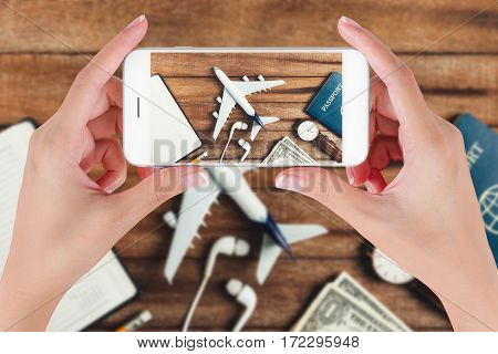 Woman hand using smart phone taking photo for preparation traveling with pencil watch money passport airplane noted book and earphone on vintage wooden background. Travel concepts.