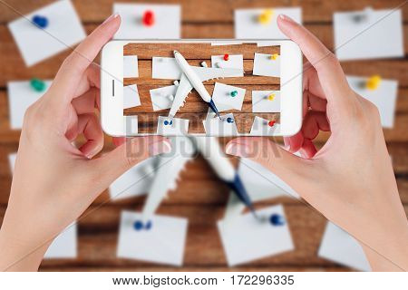 Woman hand using smart phone taking photo for preparation traveling and to do list with paper noted airplane and colorful push pin on vintage wooden background. Travel concepts blurry background.