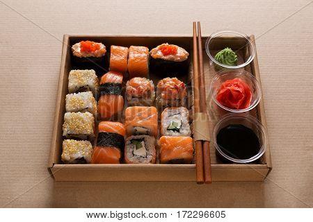 Japanese food restaurant take away in craft carton, sushi maki gunkan roll plate or platter set. Chopsticks, ginger, soy sauce, wasabi. Meals in delivery box, closeup
