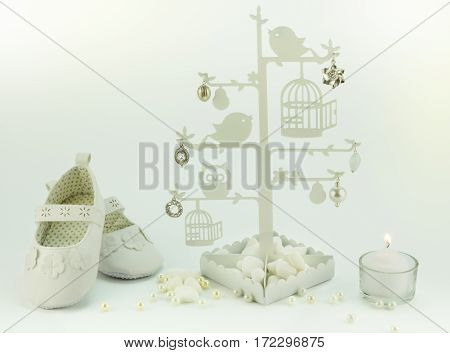Baby white invitation birthday or christening background with booties candle and charm tree