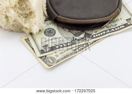 Old wallet / purse with dollar notes and a crust of bread on white background - conceptual image depicting poverty bread line in America - economic crises