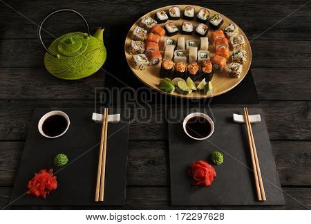Japanese food restaurant, sushi maki gunkan roll set for two or platter. Green teapot and black slate plates with chopsticks, ginger, soy, wasabi. Meals on rustic wood background