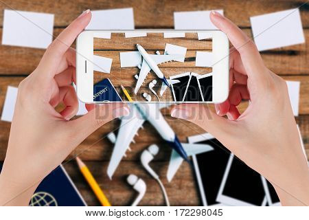 Woman hand using smart phone taking photo for preparation traveling and to do list with paper noted airplane photo frame earphone pencil and passport on vintage wooden background. Travel concepts.