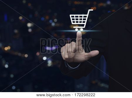 Businessman pressing shop cart icon over blur colorful night light city tower Shopping online concept