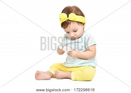 Trendy little girl, sitting with smartphone, isolated on white background