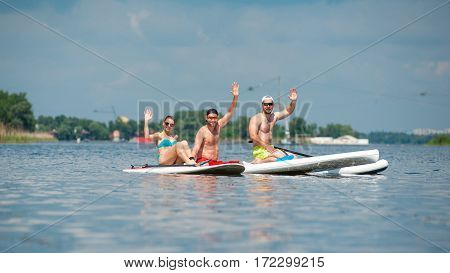 Two Man And Girl Practicing Paddle Board
