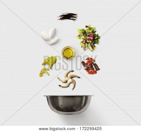 Cooking healthy food, seafood salad, isolated on blue. King prawn, shrimps, lettuce, avocado, mozzarella and other ingredients over steel mixing bowl