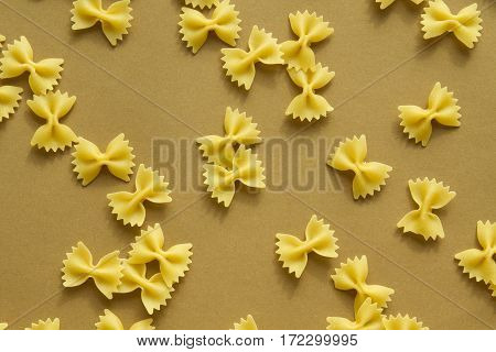 Pasta bow shape on the brown background