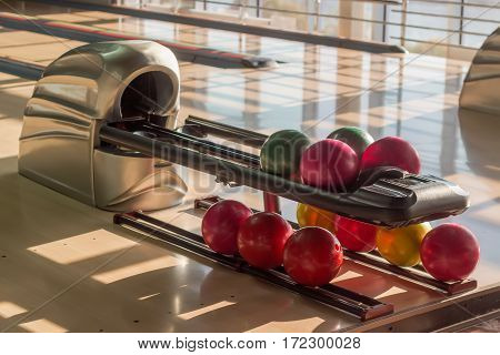Colored bowling balls with a three finger holes on the ball return device in a modern pin bowling alley