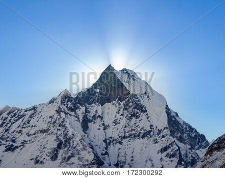 Mountain peak covered glaciers and rays of rising sun from behind him against the background of the sky early morning in the Himalayas