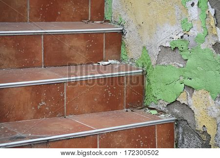 Detail of red staircase and rotting plaster on the wall