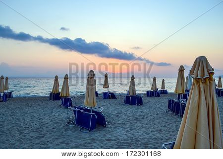 Empty beach early morning. Closed parasols and sunbeds stacked