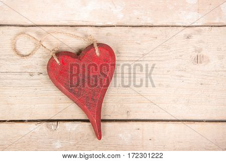 Red wooden heart on a wooden background seen from above as wishing card with space for text