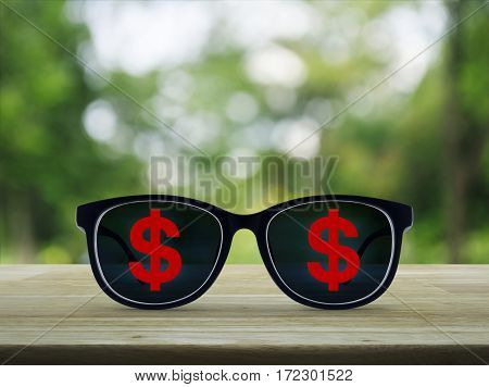 Dollar currency icon with eye glasses on wooden table over blur green tree background Business success concept