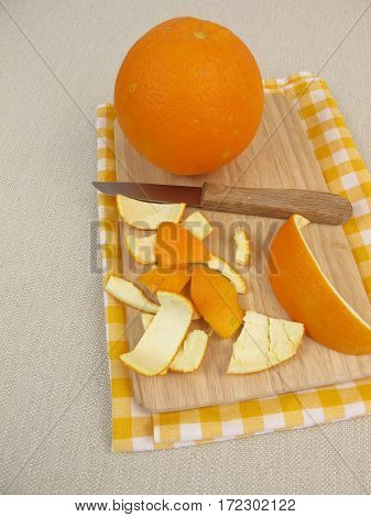 Untreated orange peel on wooden board with knife