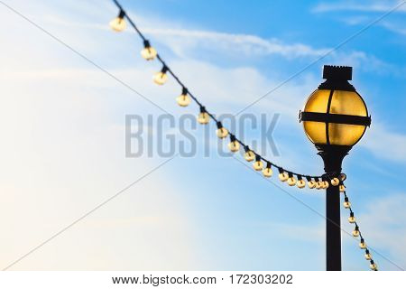 Yellow illuminated awry lamppost and string of lights at day with blue sky background color gradient to white (copy space)
