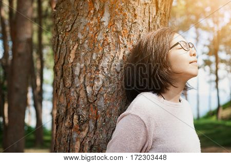 Happiness concept. Woman smiling and breathing fresh air at pine forest with sunlight.