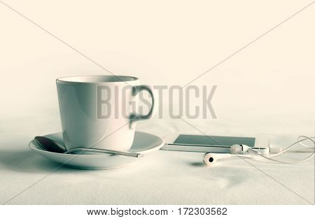 Coffee Cup With Earphones And Phone Media Portable On White Table Background.