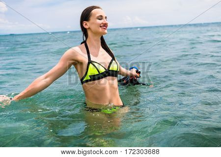 Girl with diving goggles in shallow water of tropical sea having fun in her summer vacation